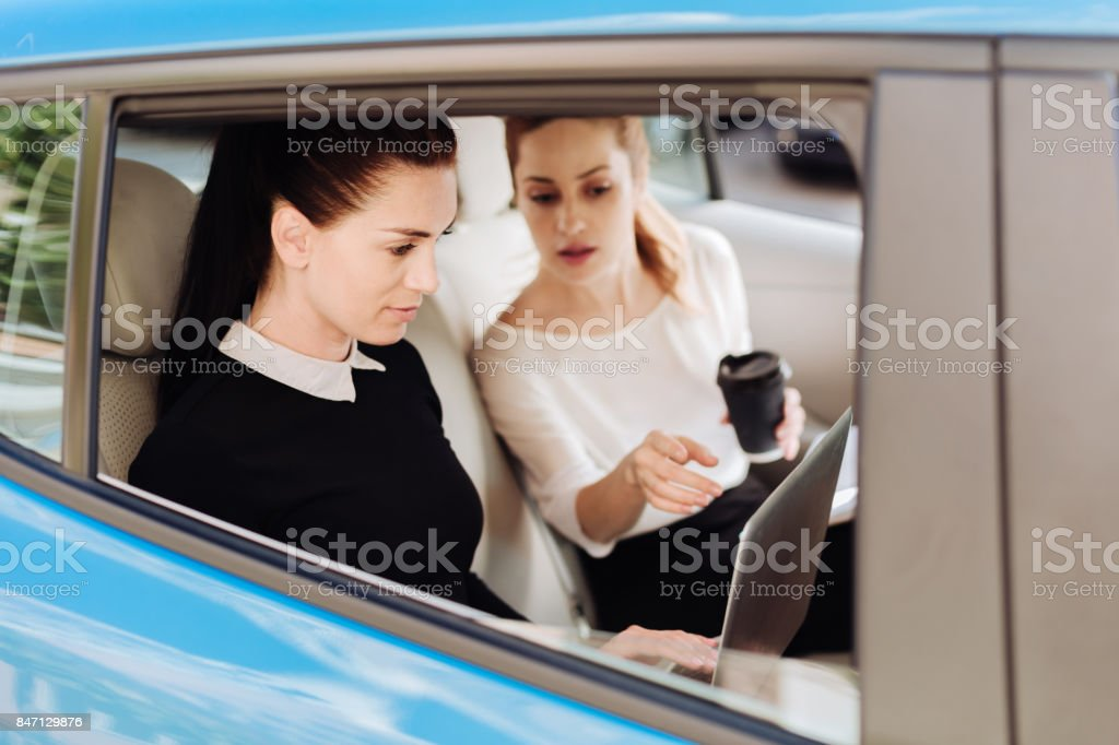 Nice pleasant woman pointing at the laptop screen stock photo