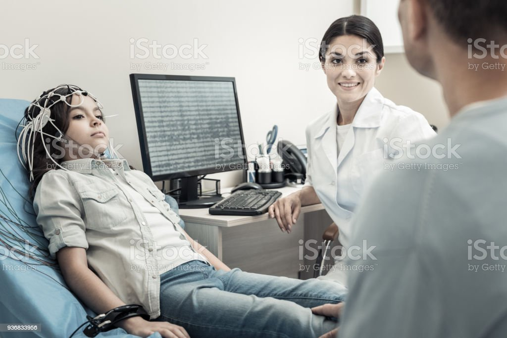 Nice positive doctor sitting in front of the computer stock photo