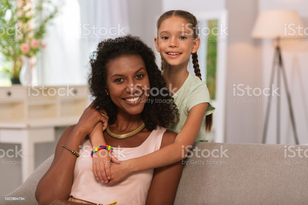 Nice positive little girl hugging her mother stock photo