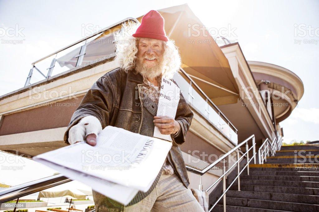 Nice positive man distributing newspapers royalty-free stock photo