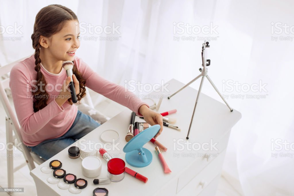 Nice pre-teen girl reviewing makeup products live stock photo