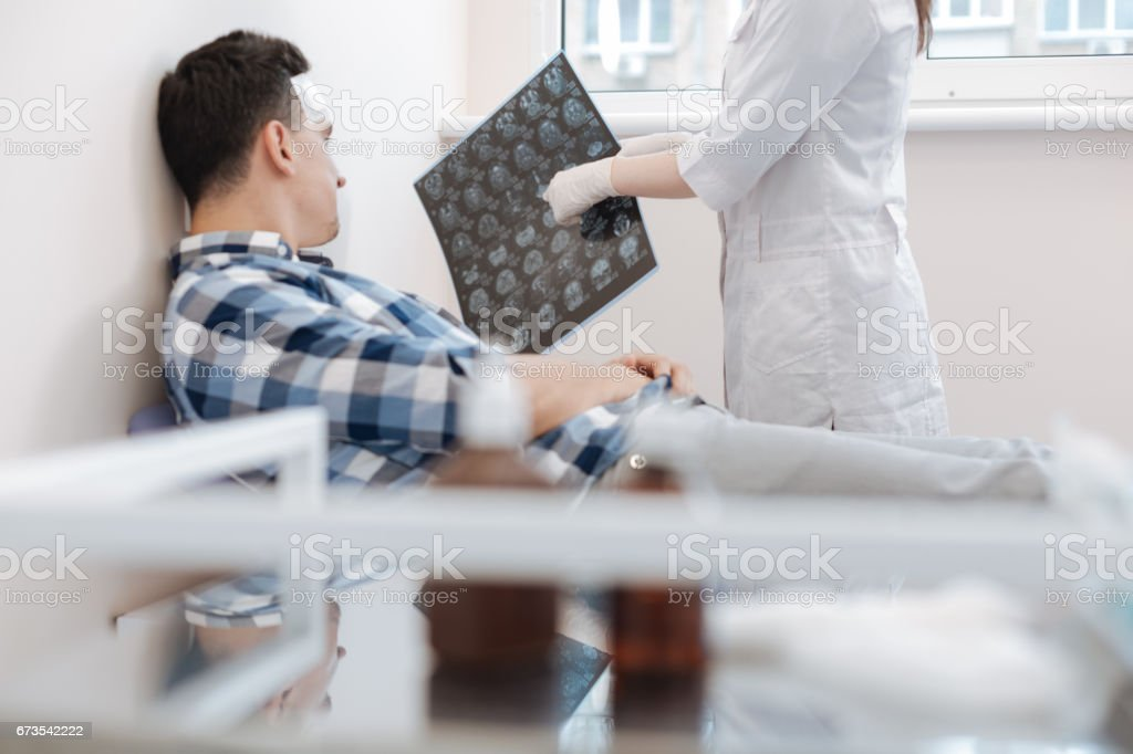 Nice professional doctor pointing at the X ray photo stock photo