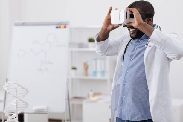 Nice professional scientist testing 3d glasses New way of research. Nice professional enthusiastic scientists standing in the middle of his office and testing 3d glasses and being excited about it dna purification stock pictures, royalty-free photos & images