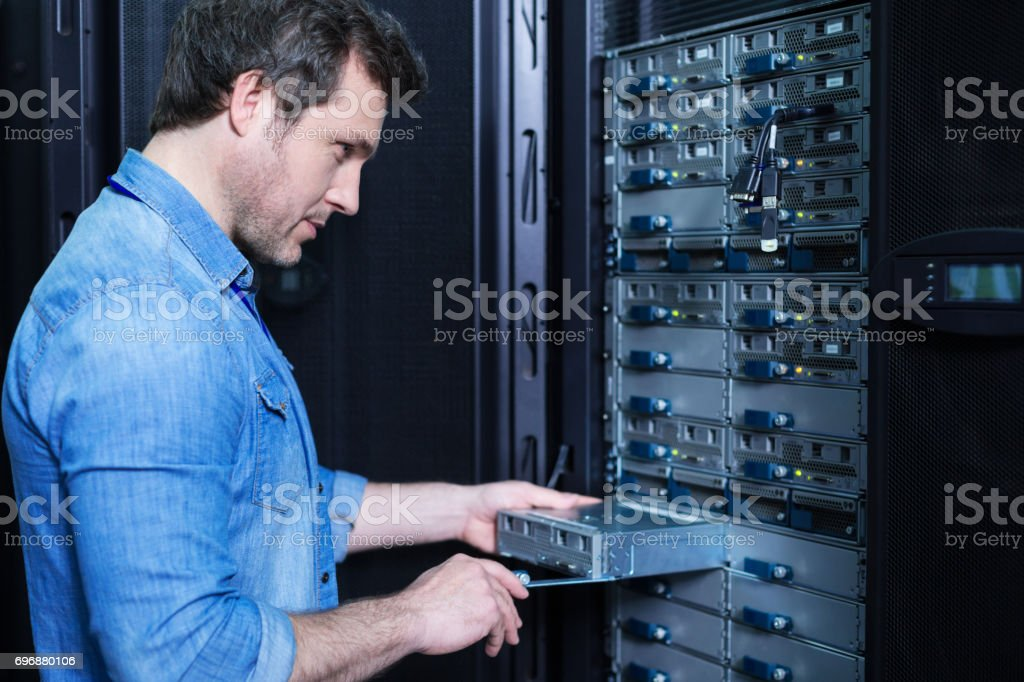 Nice professional technician installing the blade server stock photo