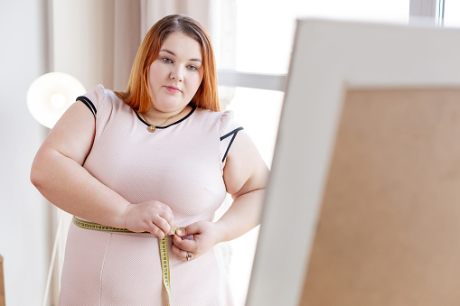 istock Nice red haired woman wanting to lose weight 1140647297