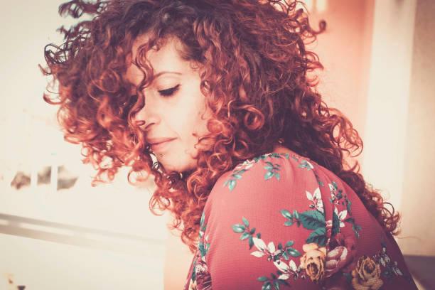 schöne rote porträt eines mädchens rotes haar verloren in ihren gedanken allein zu hause. warme farben und töne, geschlossenen augen und einsame, wunderschöne cacuasian junge frau - krause haare stock-fotos und bilder