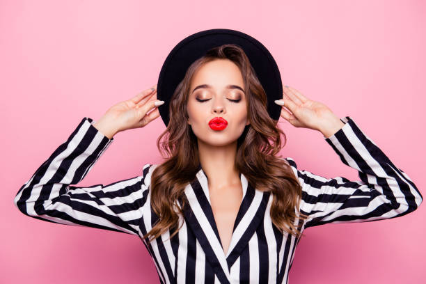 nice, rich, independent, confident, successful, luxury, sexy girl holding hat on her head with hands, having closed eyes, blowing kiss to the camera, isolated on pink background - makeup zdjęcia i obrazy z banku zdjęć