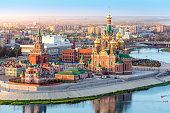 Nice view of the town at sunset. Orthodox church surrounded by beautiful red brick buildings on the city's waterfront. Volga region of Russia, the city of Yoshkar-Ola