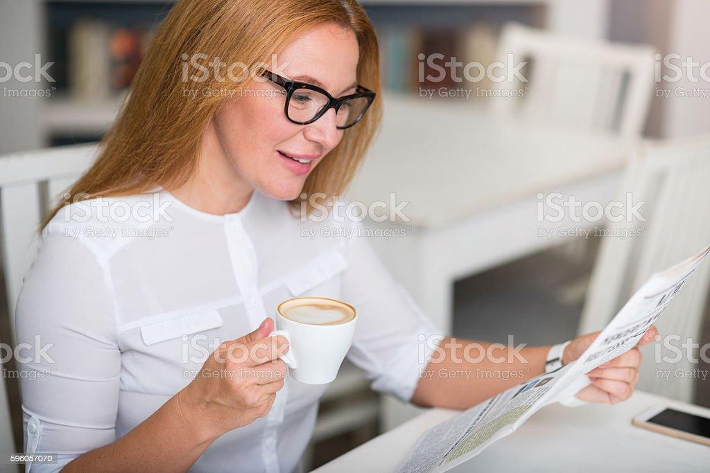 Nice senior woman reading newspaper royalty-free stock photo