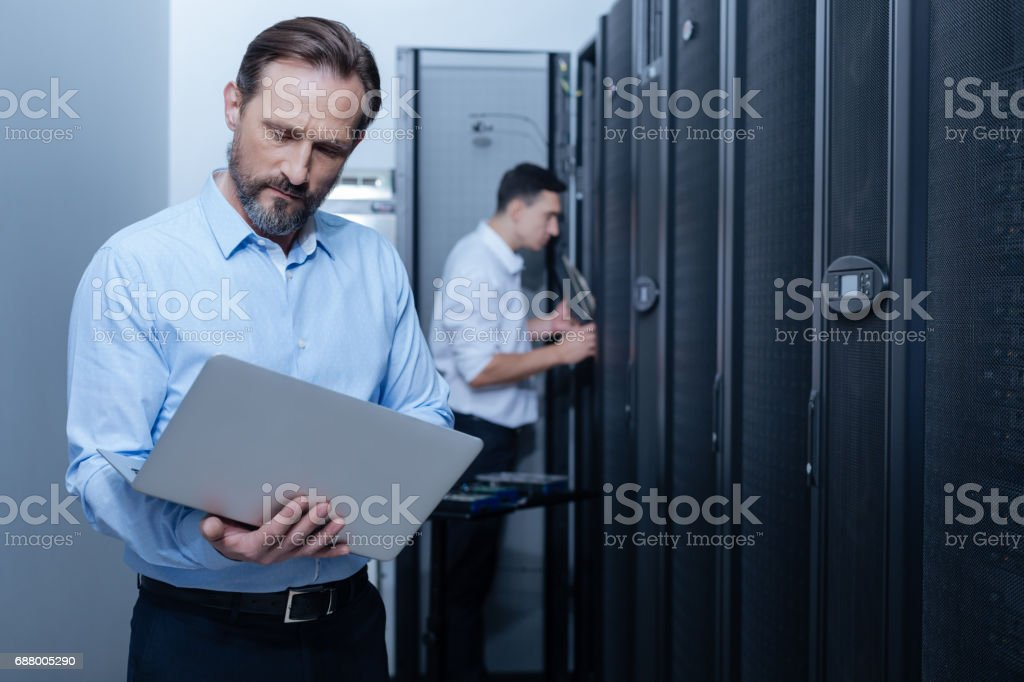 Nice serious programmer looking at the laptop screen stock photo