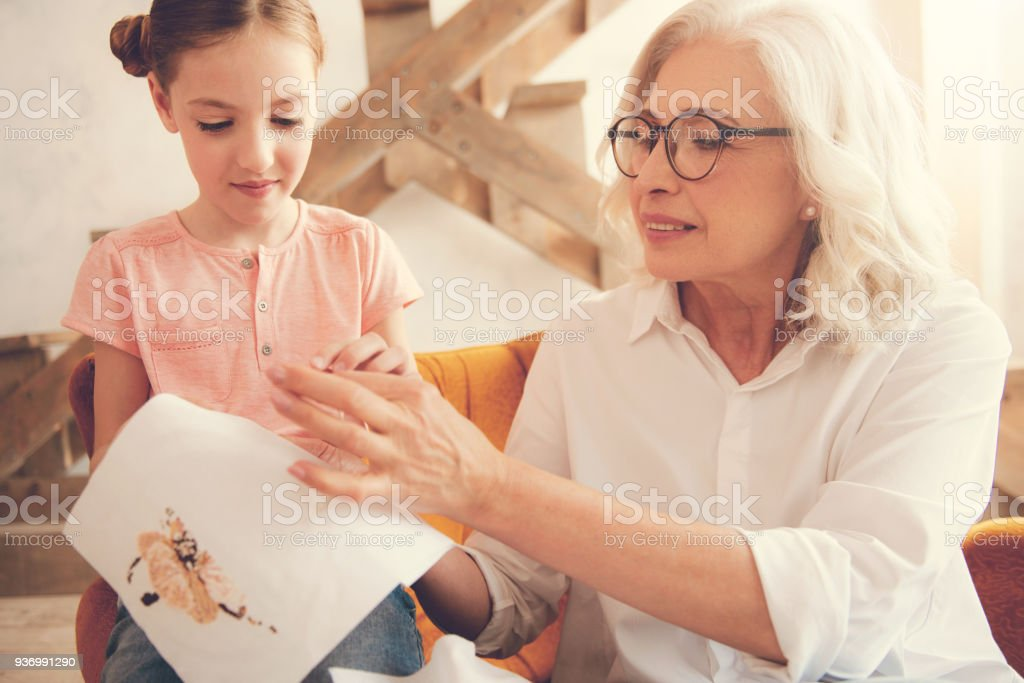 Nice smart woman teaching her granddaughter to embroider stock photo