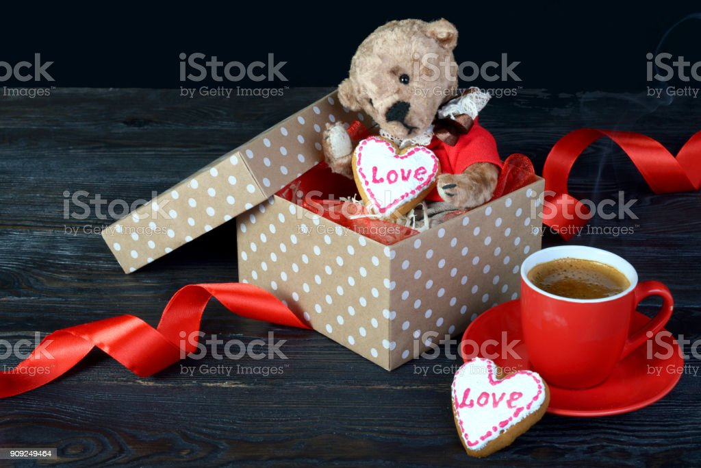 Nice teddy bear sitting in a gift box with a heart. In the hands of a cookie with the inscription 'love' and red cup of coffee with smoke. Concept Valentine's Day or a gift for a loved one. On a dark wooden background. stock photo
