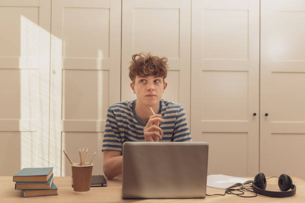 A nice teenage boy in headphones uses the laptop and learns at the desk in his room. He takes notes with a pencil. Distance learning because of the epidemic coronavirus – zdjęcie