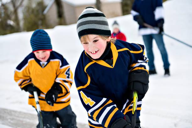schöne zwei bruder in street hockey zu spielen und spaß haben - bruderschaft stock-fotos und bilder