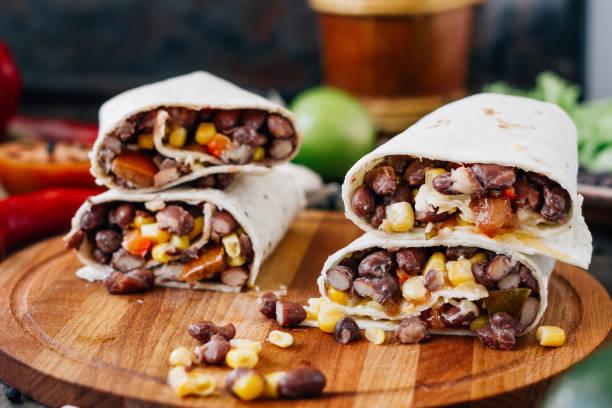 Nice vegetarian burrito over black table on wooden board. stock photo