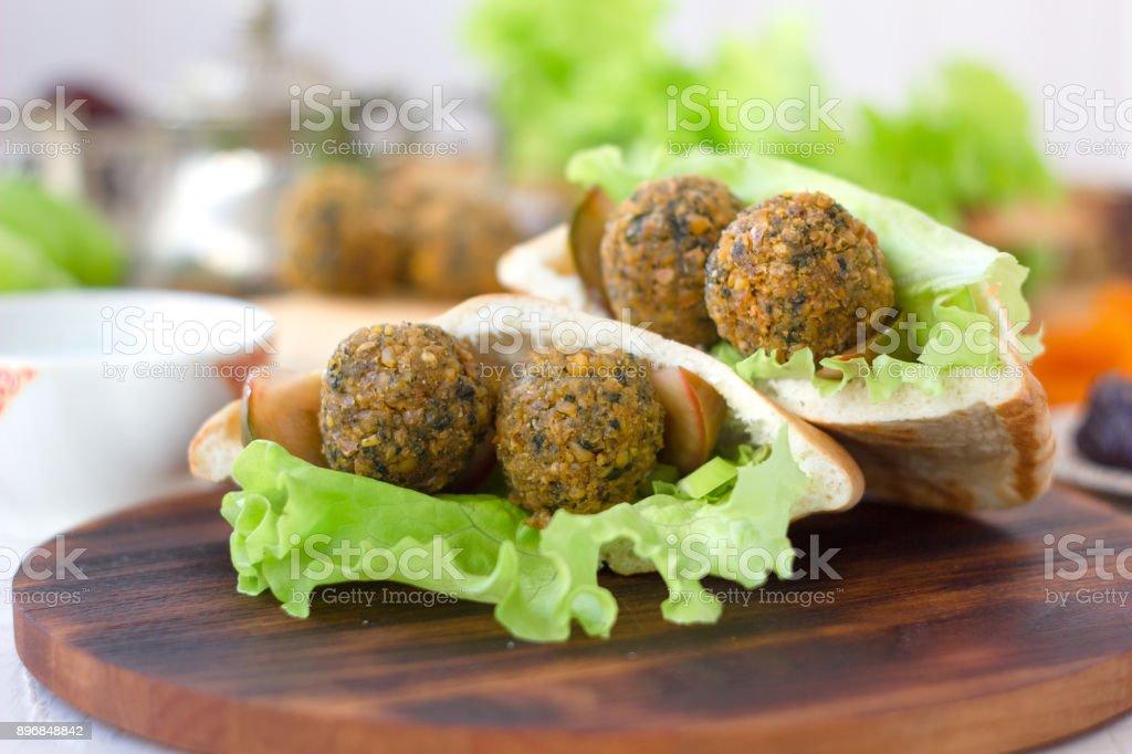 Nice vegetarian falafel in pita bread on wooden board. stock photo