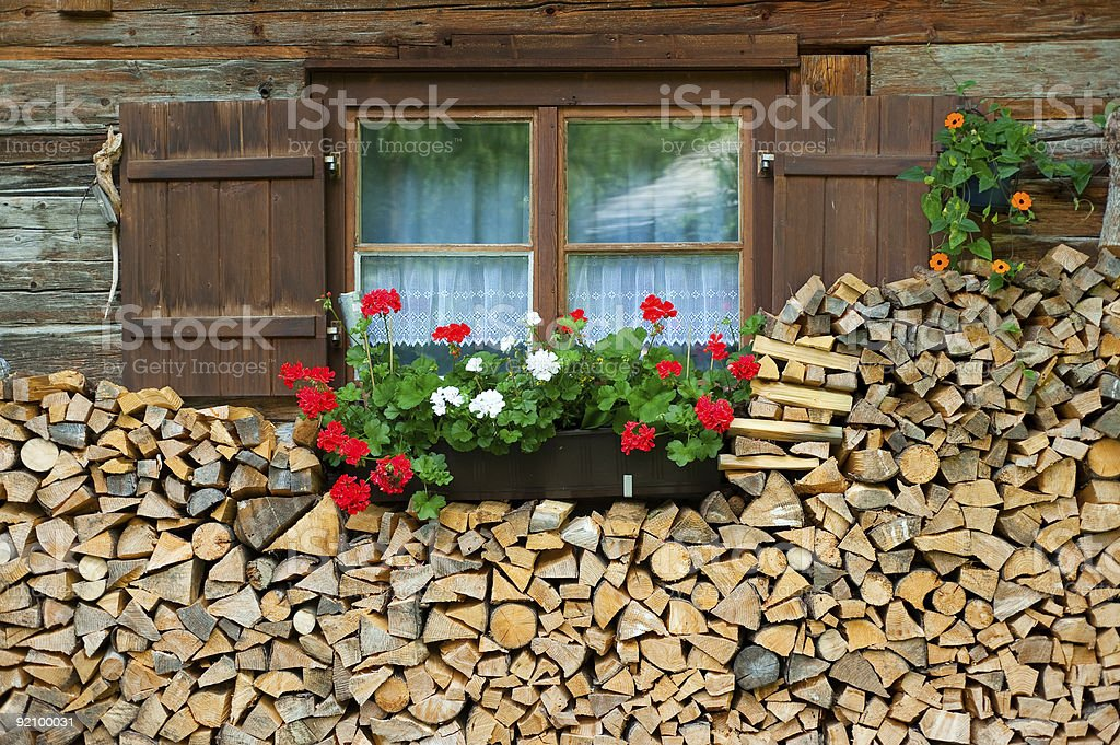 Nice window for a wooden cabin surrounded by firewood stock photo