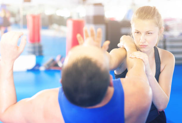 Nice woman is fighting with trainer Nice woman is fighting with trainer on the self-defense course for woman in sport club self defense stock pictures, royalty-free photos & images