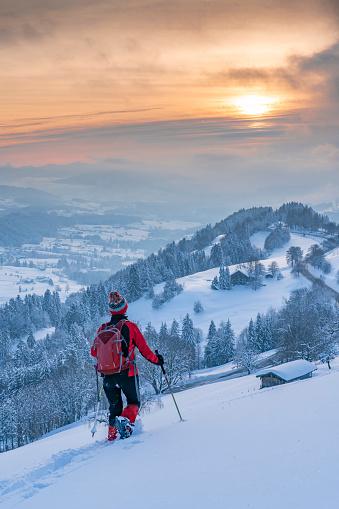 nice active senior woman snowshoeing in the Allgaeu Alps near Oberstaufen with view into the Bregenzerwald, Vorarlberg, Austria