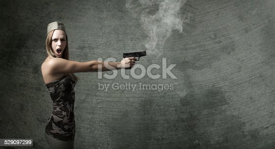 497607484 istock photo nice woman soldier shooting with rifle an empty space 529097299