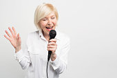 Nice woman standing on the left side of the frame and singing her favourite song. She likes to do that. Isolated on white background.