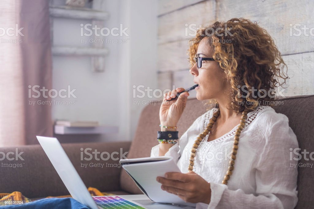nice woman type on a laptop working at home free and happy. thinking looking outside stock photo