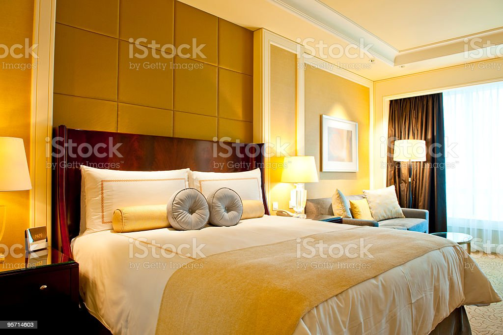 A nice yellow hotel room with one bed royalty-free stock photo