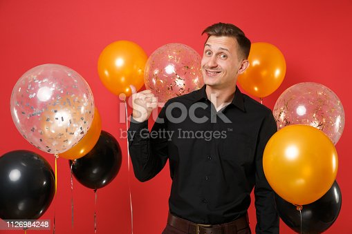 istock Nice young man in black classic shirt celebrating pointing thumb aside on red background air balloons. St. Valentine's International Women's Day, Happy New Year, birthday mockup holiday party concept. 1126984248
