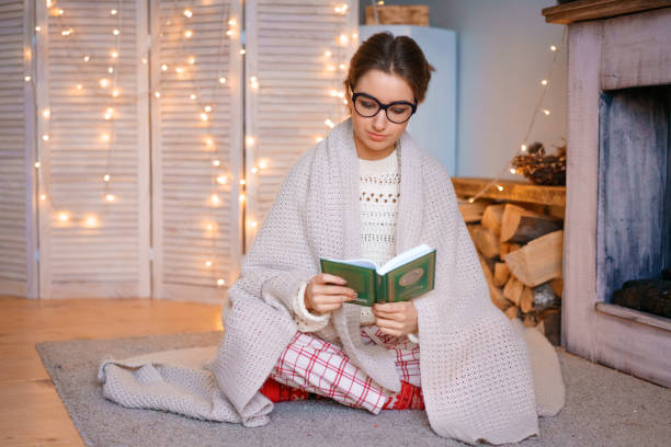 A nice young woman with glasses is sitting by the fireplace in a blanket reading a book . Cozy atmosphere light garlands stock photo