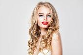 化粧と金髪のウェーブのかかった髪と素敵な若い女性。かわいい女の子の肖像画