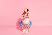 ピンクのパステル背景上に孤立した自由な時間を持つ椅子の上に座って縞模様の t シャツジーンズを着て素敵な魅力的な華やかな壮大な素敵な輝き陽気な陽気なの女の子