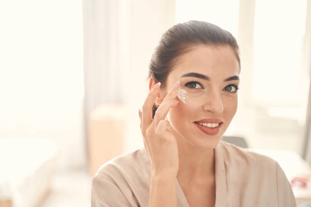 Nice-looking young woman moisturizing skin under her eyes stock photo
