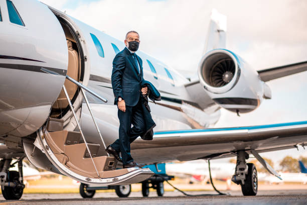 Nicely dressed businessman getting off the plane wearing protective face mask stock photo