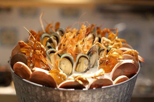 schön garnelen, muscheln, meeresfrüchte auf eis in einen eimer gelegt. essen & trinken. - esszimmer buffet stock-fotos und bilder