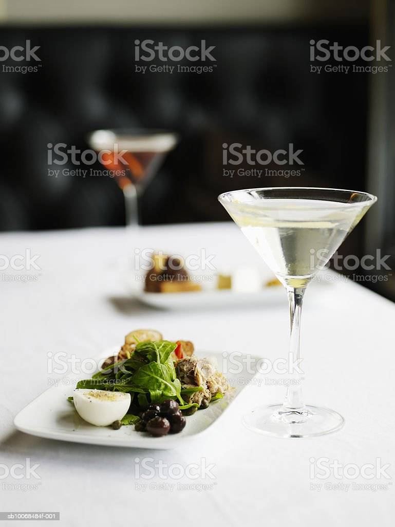 Nicoise salad with arugula, olives, tuna, hardboiled egg and capers with vesper cocktail Стоковые фото Стоковая фотография