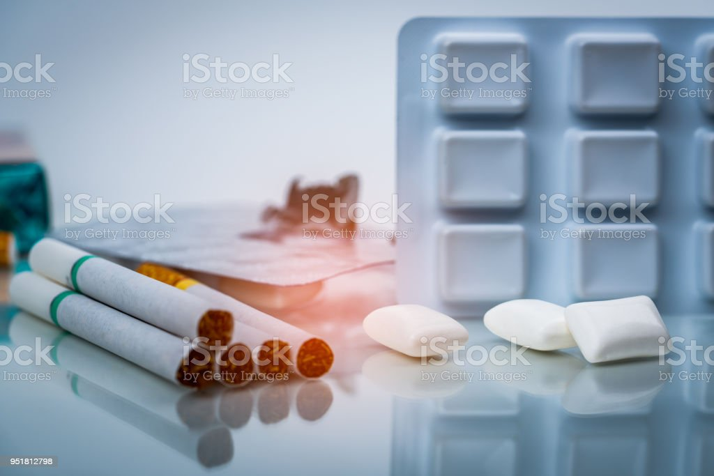 Nicotine chewing gum in blister pack near pile of cigarette. Quit smoking or smoking cessation and lung cancer concept. 31 May : World no tobacco day. stock photo