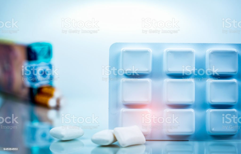 Nicotine chewing gum in blister pack on blurred background of cigarette pack.  Medicine for giving up smoking. World no tobacco day concept.