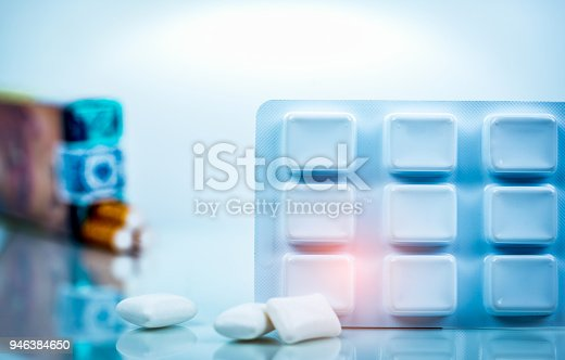 istock Nicotine chewing gum in blister pack on blurred background of cigarette pack.  Medicine for giving up smoking. World no tobacco day concept. 946384650