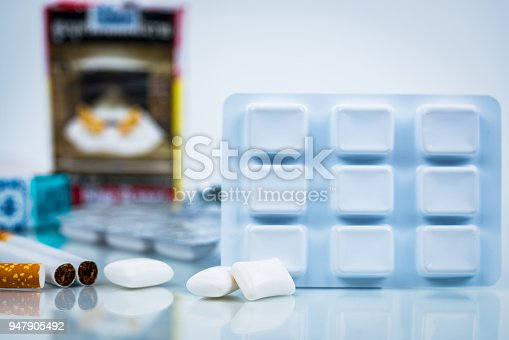 istock Nicotine chewing gum in blister pack on blurred background of cigarette pack.  Medicine for giving up smoking. World no tobacco day concept. 947905492
