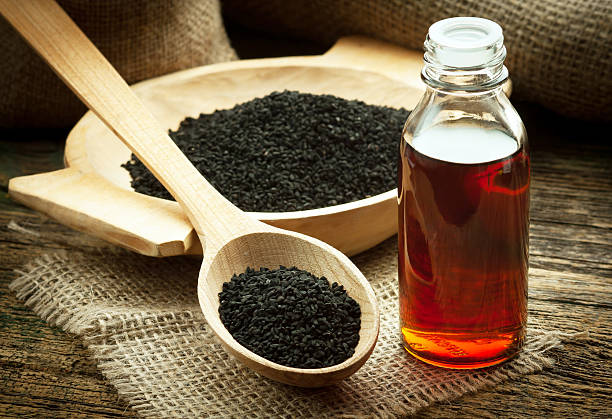 Nigella sativa oil Nigella sativa (Black cumin) on wooden spoon and essential oil. Real oil from nigella looks like dark honey cooking oil stock pictures, royalty-free photos & images