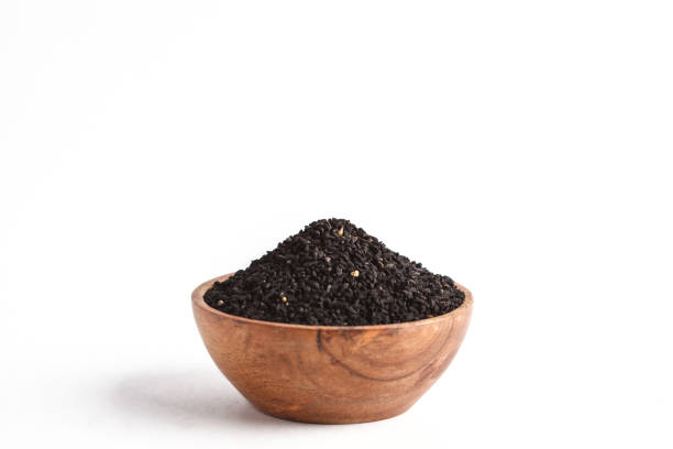 Nigella sativa or Black cumin in wooden bowl on white background, copy space, isolate stock photo