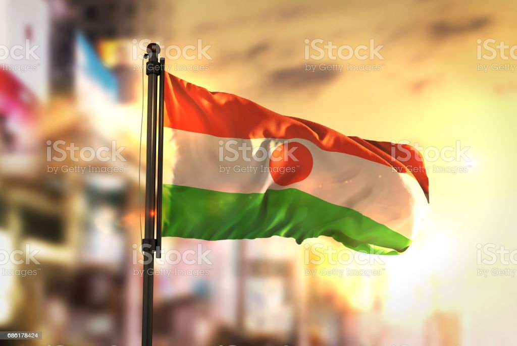 Niger Flag Against City Blurred Background At Sunrise Backlight stock photo