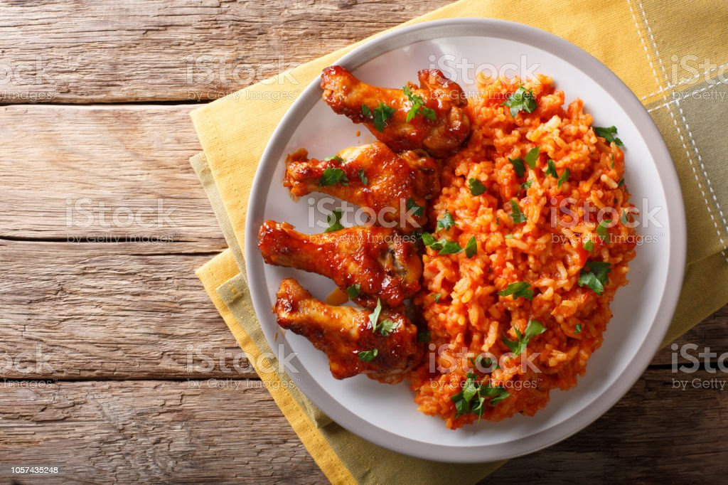 Nigerian food party: Jollof rice with fried chicken wings close-up. Horizontal top view stock photo