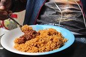 a guy eating Nigerian jollof rice