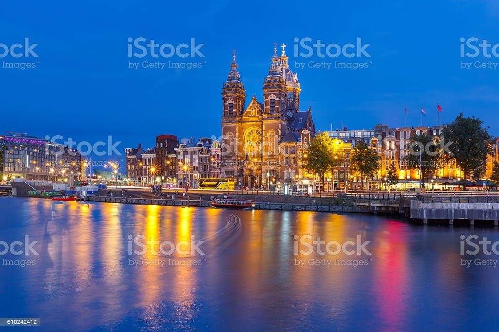 Night Amsterdam canal and Basilica Saint Nicholas stock photo