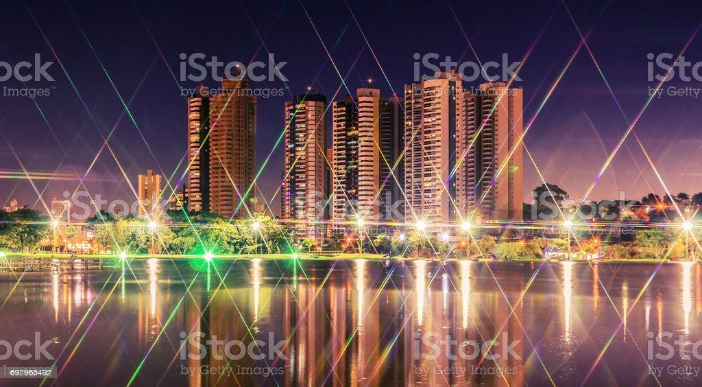 Noite em um lago de um parque com a cidade no fundo - foto de acervo