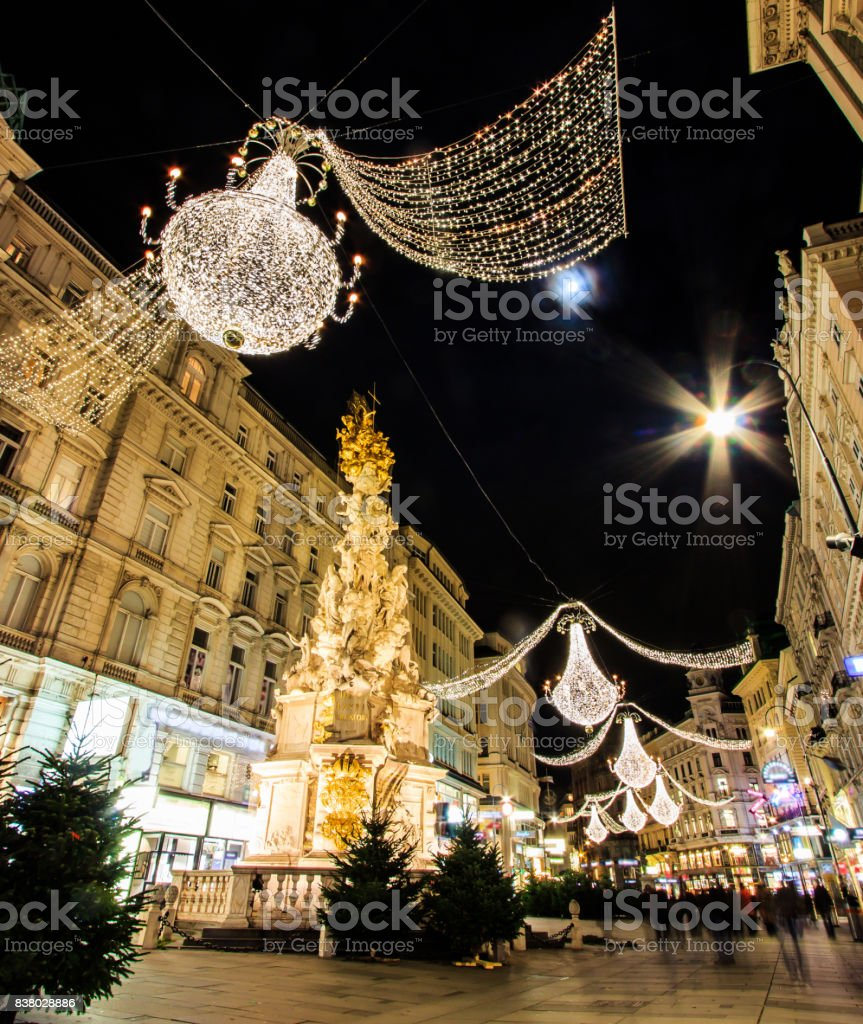 Night Atmospheric View, Motion Blurred of Graben, Busy Crowded Vienna's Shopping Street with Memorial Plague Column Pestsaule as foreground, Vienna, Austria, Europe. stock photo