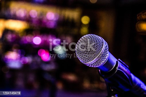 Microphone set up with lights for a comedy music show in a bar.