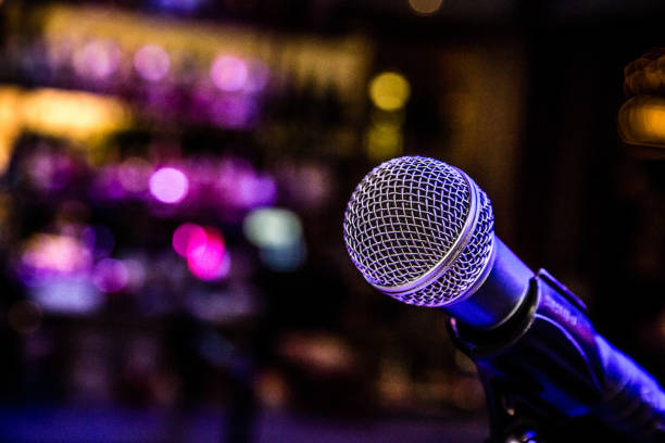 Night Bar Music Comedy Show Microphone in a Bar Microphone set up with lights for a comedy music show in a bar. microphone stock pictures, royalty-free photos & images