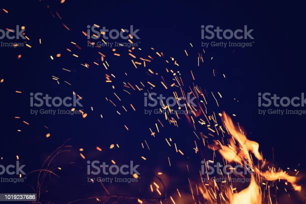 Photo of Night bonfire with sparks. Fire background with copyspace